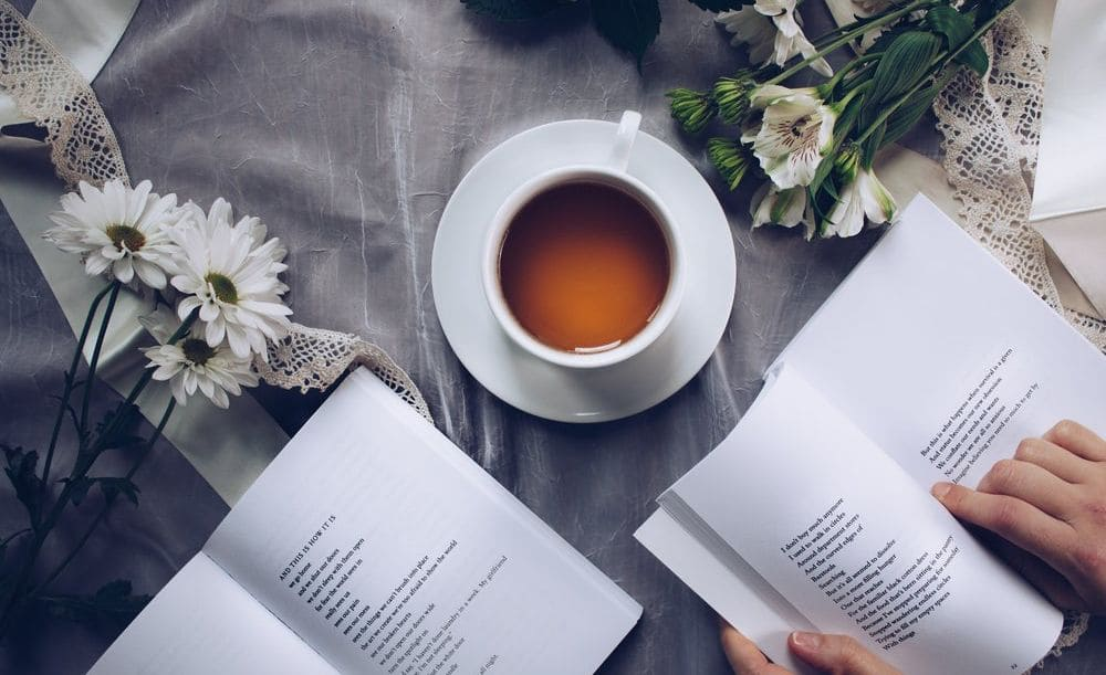 Image of a woman reading books with a cup of herbal tea
